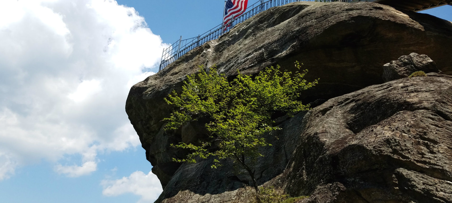 The American flag flies over a large granite monolith