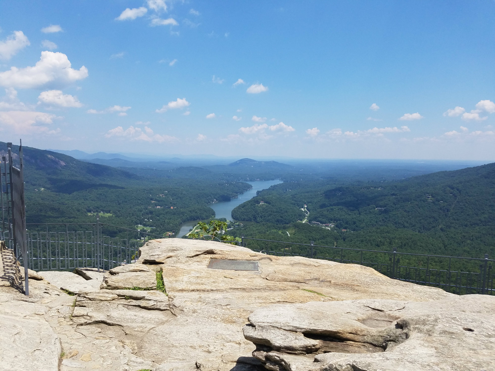 View of expansive tree-filled landscape and lake from the top of a large rock