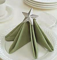 Green napkin on a white plate folded like a Christmas tree with a small star on the top