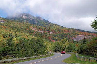 Red car on a road leading to a mountain covered in the start of fall color