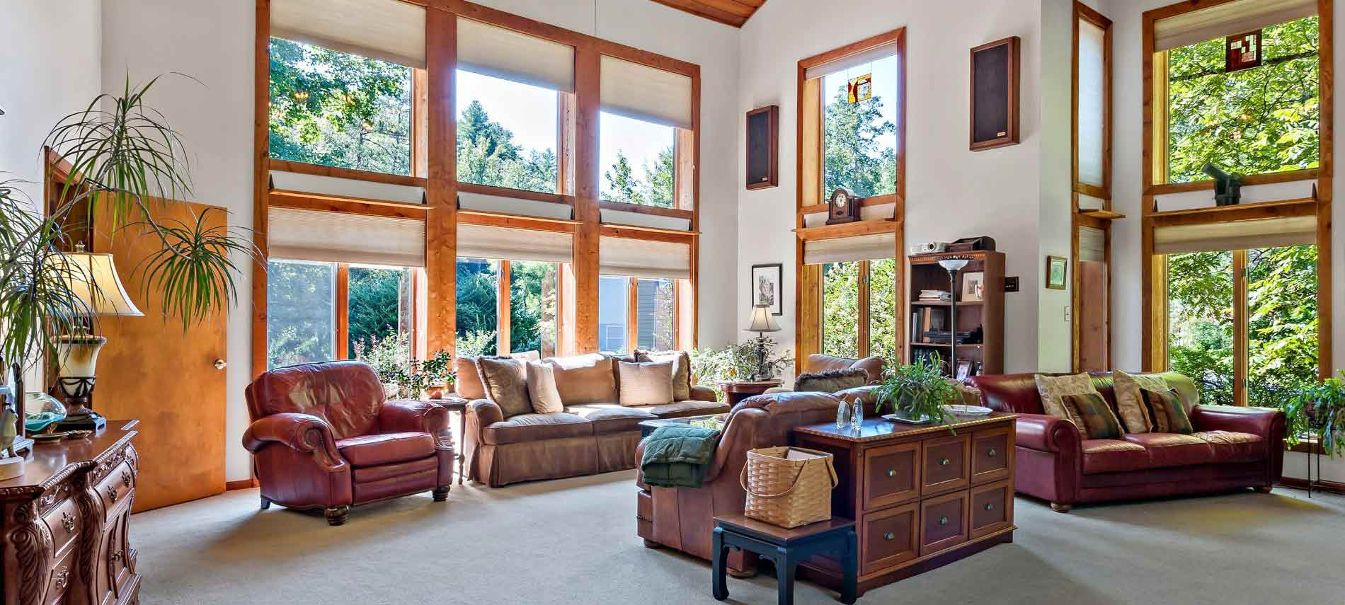 Spacious interior sitting area with multiple couches and love seats underneath high ceiling with tall windows allowing in sunlight.
