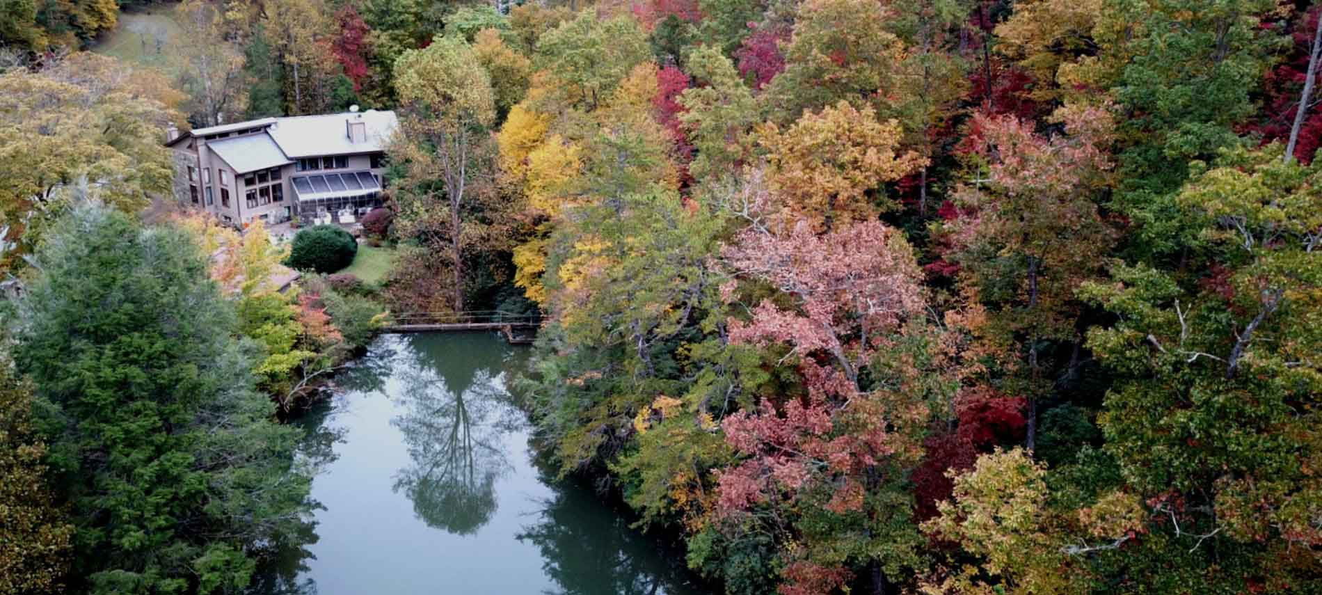 Aerial exterior view of the Inn of Mill Creek and propery including the autumn changes upon the leaves surrounding a pool of water.