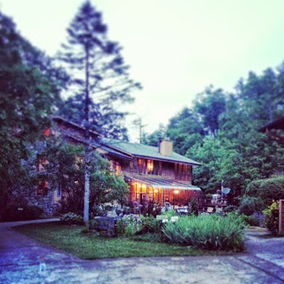 Lodge style bed and breakfast surrounded by trees at twilight