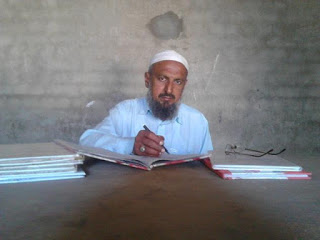 Pakistani school teacher sitting at a table writing in a book