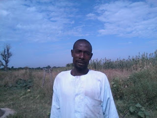 Nigerian farmer with a white shirt standing outside in a field