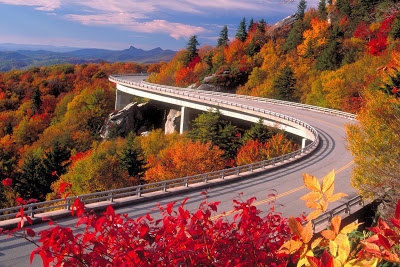 Road curving around a mountain full of brilliant fall foliage