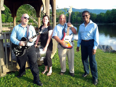 Two men with guitars, a woman with a drum and a fourth band member posing by a lake and gazebo