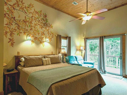 Bedroom with handpainted tree branch and leaves mural on the wall above the bed