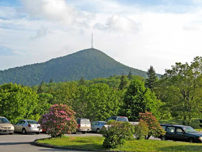Tall mountain peak with radio tower on top and parking lot of cars in front of it