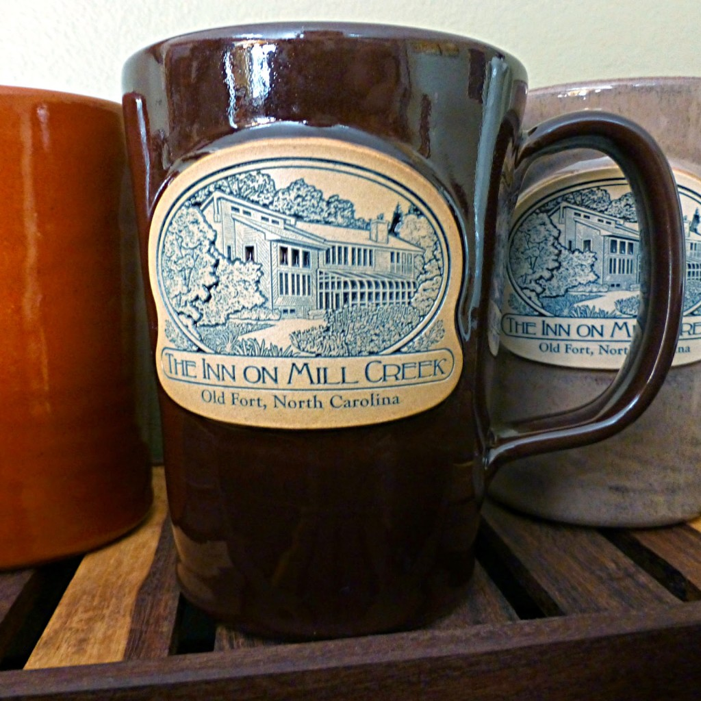 Dark brown pottery mug on a wooden rack with a logo that says The Inn on Mill Creek