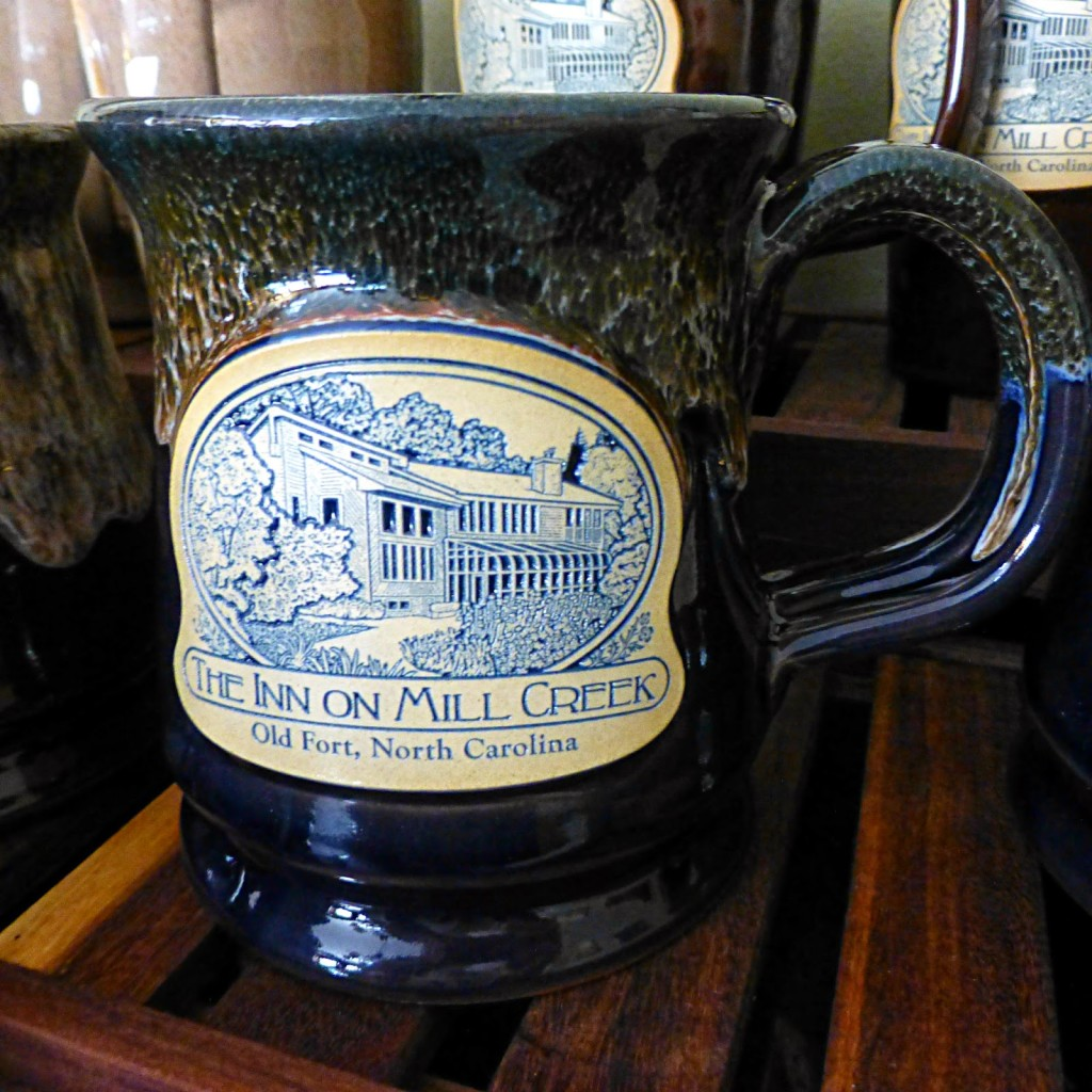 Dark blue pottery mug with marble glaze on top and logo that says The Inn on Mill Creek