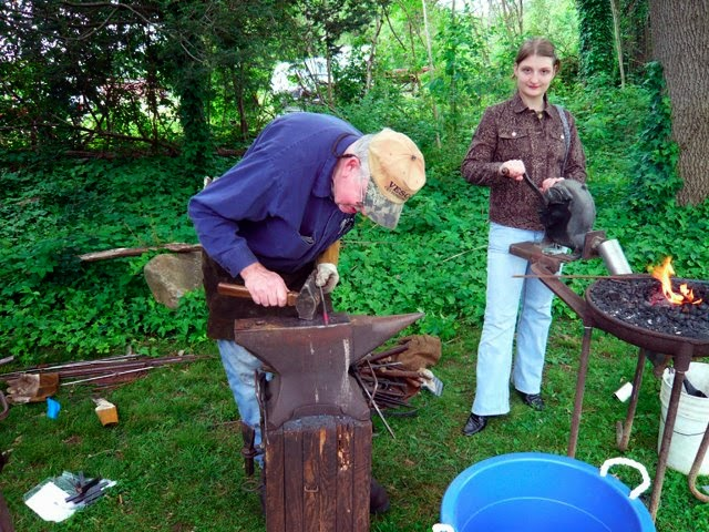 Man with a baseball cap forging iron with a hammer and anvil while a young girl watches