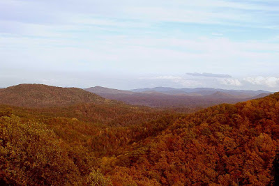 View of mountain ranges in striking orange and red fall colors