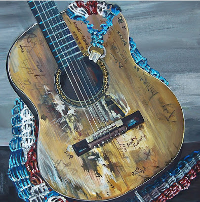 Painting of a guitar with autographs on it and a red, white and blue guitar strap