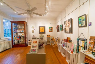 Large room with windows on one side, a display cabinet with art in it and art hanging on the walls